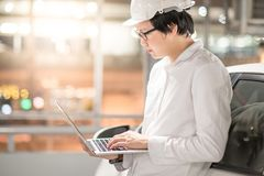 Young Asian Engineer or Architect working with laptop. Computer while wearing a personal protective equipment safety helmet at construction site. Engineering royalty free stock image