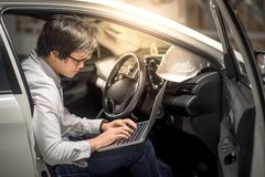 Young Asian Engineer or Architect working with laptop in his car Stock Photos