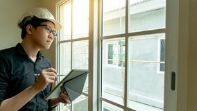Asian engineer using tablet on construction site. Young Asian engineer with helmet and eyeglasses using digital tablet looking through the window at construction stock images