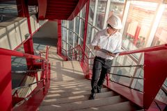 Young Asian Engineer holding files at construction site. Young Asian Engineer or Architect holding files and architectural drawing wearing personal protective Royalty Free Stock Image