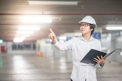 Young Asian Engineer holding files at construction site. Young Asian Engineer or Architect holding files and pointing his hand while wearing personal protective Royalty Free Stock Image