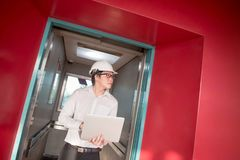 Young Asian engineer holding laptop in elevator Stock Image