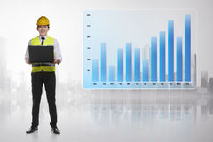 Young asian engineer man with laptop standing beside income grap Stock Photography