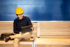 Young Asian engineer man wearing helmet working with tablet stock image