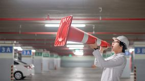 Asian engineer yelling though traffic safety cone in parking lot Stock Photography
