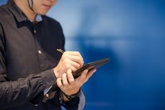 Young Asian engineer man writing on tablet. Working with digital device concept Stock Photo
