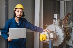 Young Asian engineer poses near heavy machinery stock image