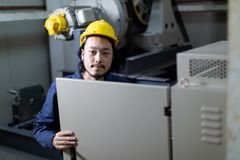 Young Asian engineer use notebook seting to machinery royalty free stock photos