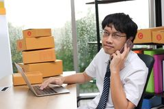 Young Asian entrepreneur owner talking on phone at workplace at home. Start up small business.  royalty free stock image