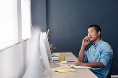 Young Asian entrepreneur talking on a cellphone in an office. Focused young Asian designer reading paperwork and talking on a cellphone while sitting at his desk Stock Photos