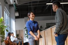 Young Asian entrepreneurs in a discussion in a co working space.  royalty free stock photo