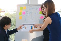 Young Asian executive boss meeting with employee explaining strategies on flip chart in boardroom.  stock image