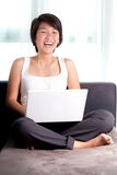 Young Asian executive laughs while chatting online Royalty Free Stock Images
