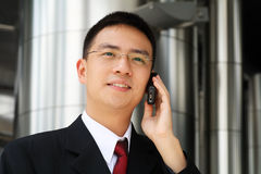 Young asian executive talking on handphone. Young asian executive talking on a handphone dressed in suit Royalty Free Stock Photography