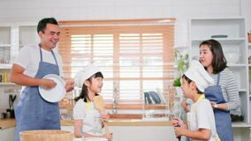 Young Asian family of mother, father, daughter and son enjoy play, sing, dance together in home kitchen