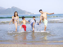 Young asian family playing on beach Royalty Free Stock Image