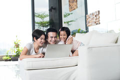 Young Asian family using the computer together at home. Happy Asian family looking at the laptop together Stock Photos