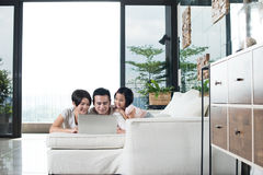 Young Asian family using the computer together at home. Happy Asian family looking at the laptop together at home Royalty Free Stock Photos