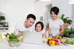 Young Asian family using the computer together at home. Young Asian family looking at the laptop together in the kitchen at home Stock Image