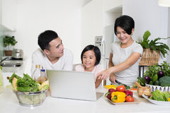 Young Asian family using the computer together at home. Young Asian family looking at the laptop together in the kitchen at home Stock Photography