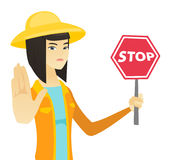 Young asian farmer holding stop road sign. Royalty Free Stock Photography
