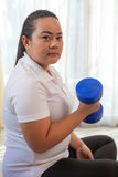 Young asian fat woman does fitness with dumbbell Stock Photography