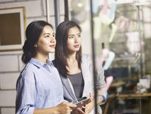 Young asian female corporate executives working together in office. Two young asian entrepreneurs teaming up analyzing business situation using adhesive notes royalty free stock photo