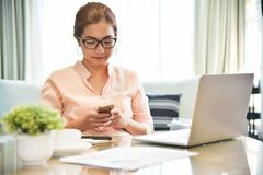 Young Asian Female creative designer using cell phone. Young Asian Female creative designer using cell phone at her workplace. A Woman doing Online shopping royalty free stock photography