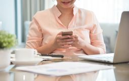 Young Asian Female creative designer using cell phone. Young Asian Female creative designer using cell phone at her workplace. A Woman doing Online shopping stock photo