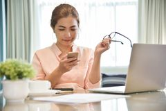 Young Asian Female creative designer using cell phone. stock image