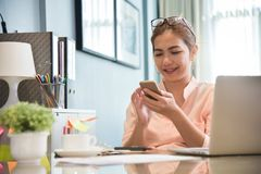 Young Asian Female creative designer using cell phone. Young Asian Female creative designer using cell phone at her workplace. A Woman doing Online shopping royalty free stock photo