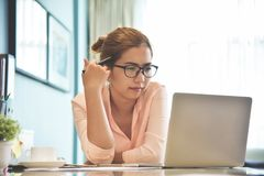 Female creative designer wear glasses thinking. Young Asian Female creative designer wear glasses thinking and working with a laptop computer at her workplace royalty free stock images