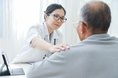 Female doctor comforting senior male patient. Young Asian Female doctor comforting senior male patient in medical office Royalty Free Stock Image