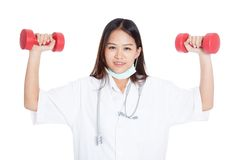 Young Asian female doctor with dumbbell in both hands Royalty Free Stock Photo