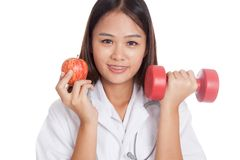 Young Asian female doctor  hold apple and dumbbell Royalty Free Stock Photos