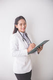 Young asian Female doctor, holding a clipboard and smiling to ca Royalty Free Stock Photography