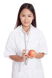 Young Asian female doctor listening to an apple with a stethosco Royalty Free Stock Photo