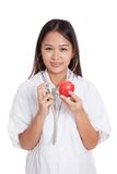 Young Asian female doctor listening to an apple with a stethosco Stock Image