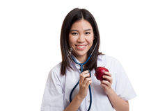 Young Asian female doctor listening to an apple with a stethosco Stock Photo