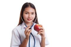 Young Asian female doctor listening to an apple with a stethosco Royalty Free Stock Images