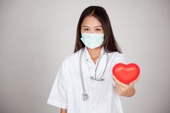 Young Asian female doctor with with mask and red heart. On gray background royalty free stock photography