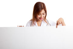 Young Asian female doctor point and look down to blank sign. Isolated on white background Royalty Free Stock Photo