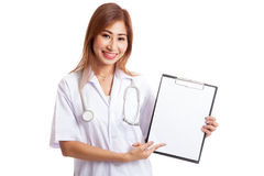 Young Asian female doctor point to a blank clipboard. Isolated on white background Stock Photography