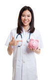 Young Asian female doctor point to a pig bank coin. Royalty Free Stock Images