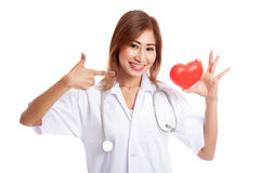 Young Asian female doctor point to red heart. Isolated on white background Stock Images