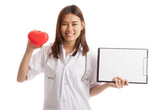 Young Asian female doctor with red heart and blank clipboard. Young Asian female doctor with red heart and blank clipboard isolated on white background royalty free stock image
