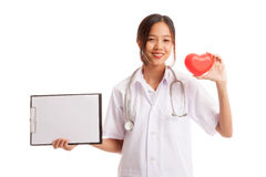 Young Asian female doctor with red heart and blank clipboard. Isolated on white background stock photo