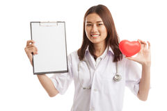 Young Asian female doctor with red heart and blank clipboard. Young Asian female doctor with red heart and blank clipboard isolated on white background stock image