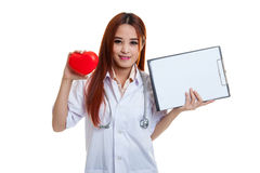 Young Asian female doctor with red heart and blank clipboard. Young Asian female doctor with red heart and blank clipboard isolated on white background royalty free stock photos