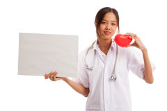 Young Asian female doctor with red heart and blank sign. Isolated on white background stock photo